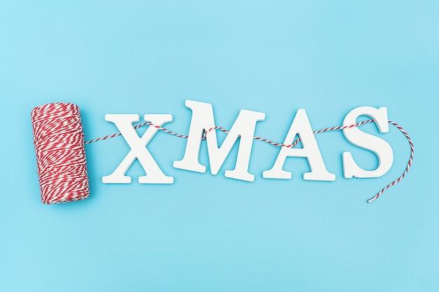 クリスマスデコレーションの赤と白のひもに白いボリューム文字からテキストクリスマス