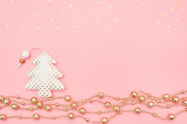 Декоративная текстильная новогодняя елка и золотая гирлянда и звезды на розовом фоне