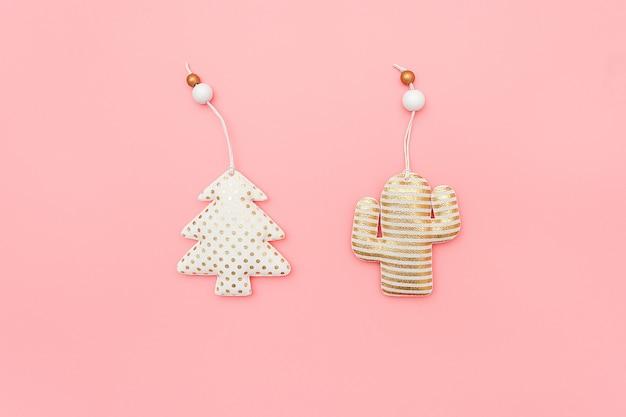 装飾織物クリスマスツリーとコピースペースとピンクの壁にサボテン。クリスマスや新年のコンセプト。