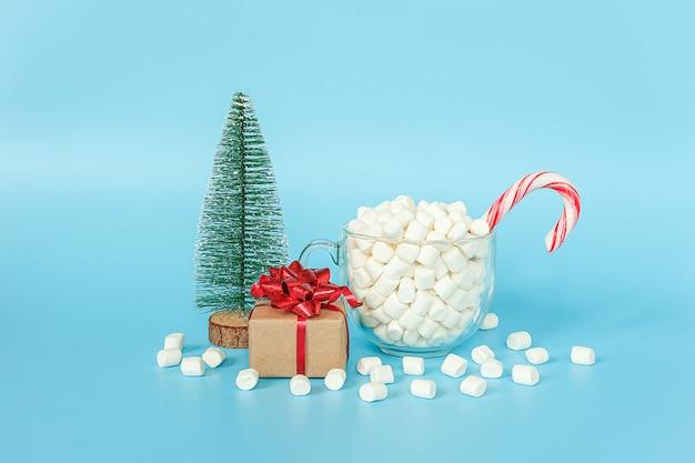 ギフトボックス、クリスマスツリー、青い壁に赤いロリポップ杖とマシュマロのカップ。