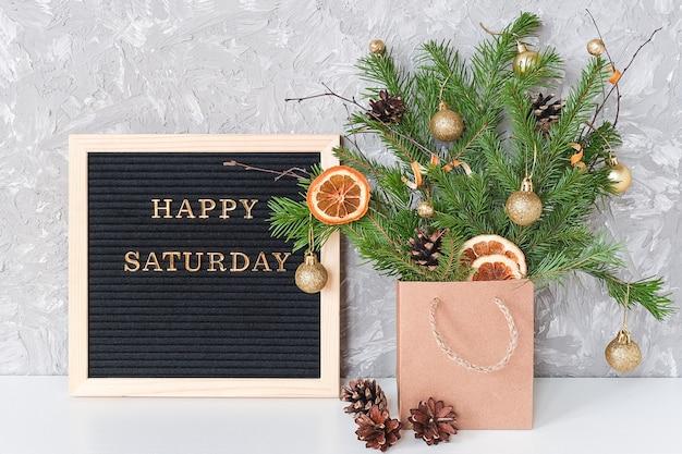 Счастливый текст субботы на черной доске письма и праздничный букет еловых веток с рождественским декором в пакете ремесла на столе.
