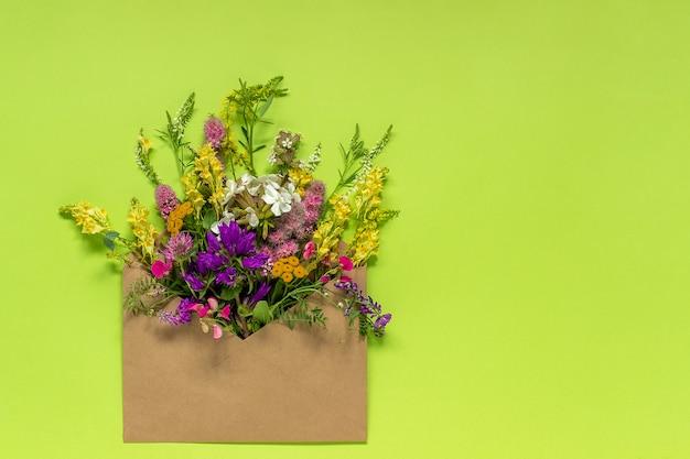 緑の背景にクラフト封筒の野の花
