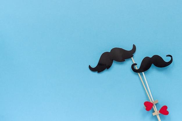 棒にカップル紙口ひげ小道具は青の背景に洗濯はさみの心を固定