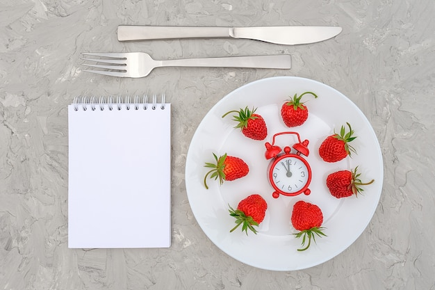 Красная спелая ягода клубники на белой тарелке, столовые приборы, красный будильник и пустой блокнот на сером камне