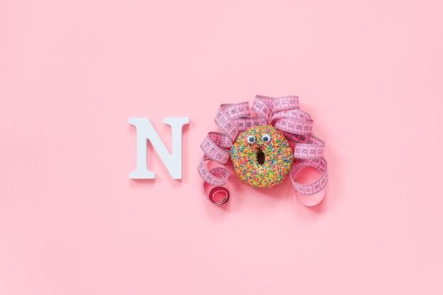 Смешное лицо женщины из пончика с глазами и волосами из сантиметровой ленты на табличке и надписью «нет»