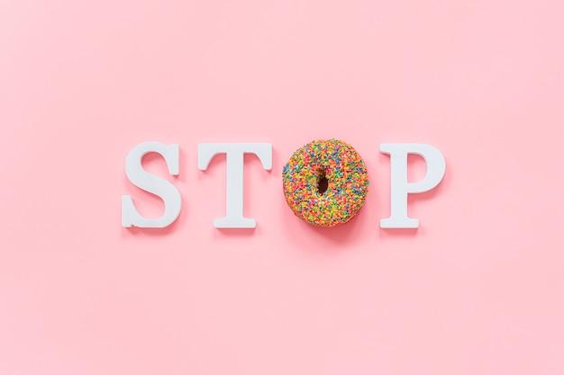 Текст стоп из белых объемных букв и глазированных красочных пончиков диета, отказ от фаст-фуда, нездоровое питание