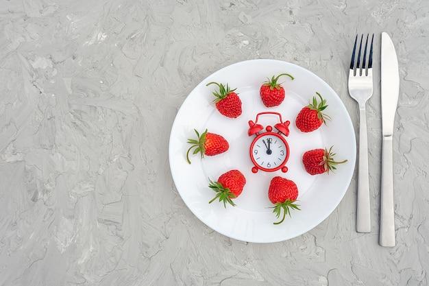 Красная зрелая ягода клубник на белой плите, столовом приборе и красном будильнике на серой каменной таблице, крупном плане.