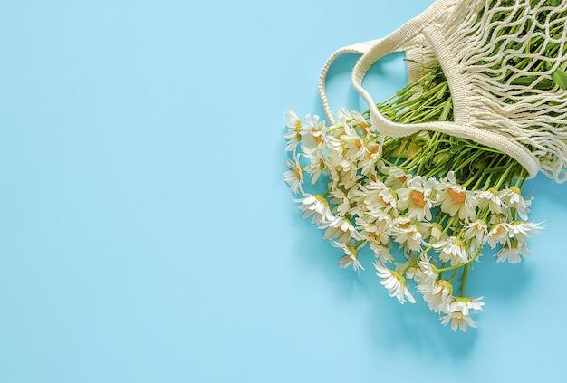 Букет полевых ромашек в многоразовой сумке из экологически чистой сетки. концепция без пластика и ноль отходов.