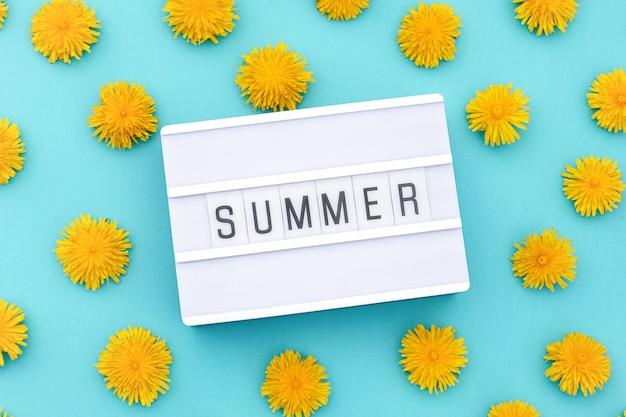 Текст лето на лайтбоксе и жёлтые одуванчики. концепция привет лето. вид сверху плоская планировка