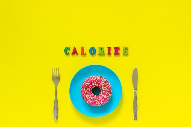 カロリーと青い皿の上のピンクのドーナツと黄色の背景にナイフフォーク。