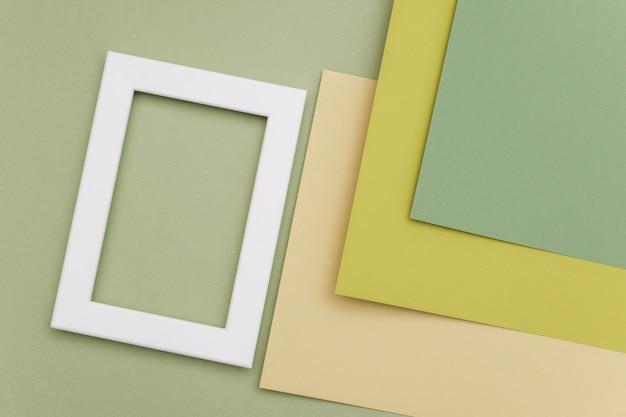 Белая рамка на фоне геометрических зеленых оттенков бумаги.