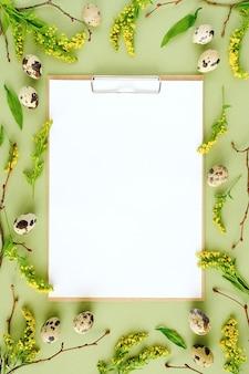 春のイースター花のフレームと白い空白の紙。天然木の枝、黄色の花、ウズラの卵、緑の背景のモックアップにクリップボードのメモ帳
