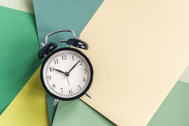 幾何学的な緑の色合いの紙の背景に黒の目覚まし時計。テキスト、デザインの最小限のスタイルコピースペース平面図テンプレート