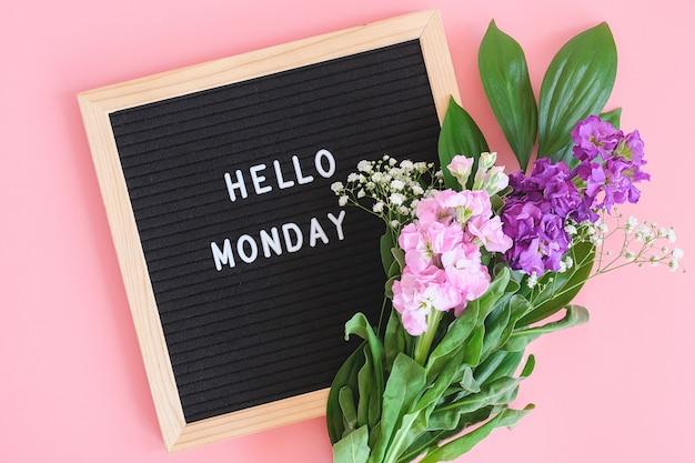 こんにちは、ブラックレターボードの月曜日のテキストとピンクの背景に色とりどりの花の花束。