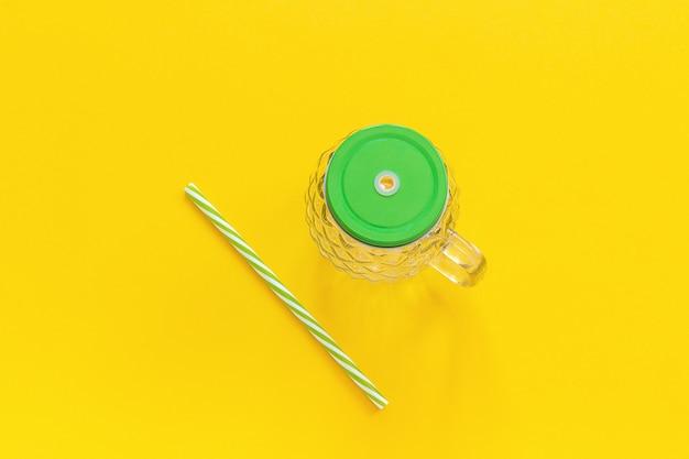 Пустую стеклянную банку в виде ананаса с зеленой крышкой и соломы для фруктовых или овощных смузи, коктейлей на желтом фоне.