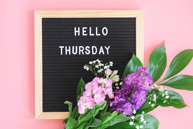 こんにちは、ブラックレターボードの木曜日のテキストとピンクの背景に色とりどりの花の花束。コンセプトハッピー木曜日。