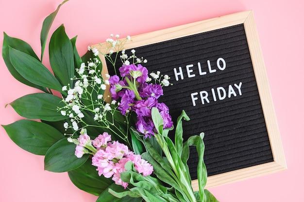 こんにちは、ブラックレターボード上の金曜日のテキストとピンクの背景に色とりどりの花の花束。コンセプトハッピーフライデー。