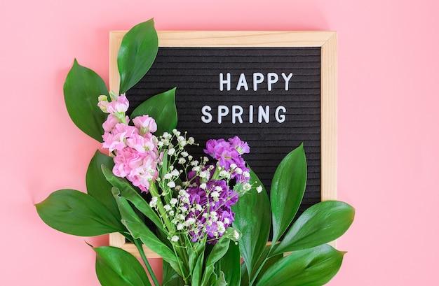 ブラックレターボードとピンクの背景の花の花束の幸せな春のテキスト。コンセプトこんにちは春、春。