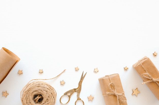 ホリデーギフトを梱包するための材料のセット。クラフト紙、ジュートコード、はさみ、白い背景の上の箱。休日ゼロ廃棄物