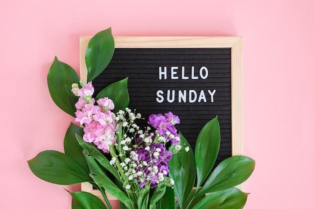 こんにちはブラックレターボードの日曜日のテキストとピンクの背景に色とりどりの花の花束。コンセプトハッピーサンデー。
