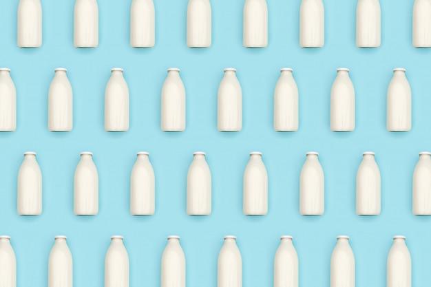 青い壁に牛乳の透明なガラス瓶で作られたパターン。フラット横たわっていたトップビュー