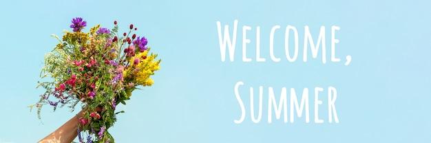ようこそ夏のテキスト。女性の手は、青い空を背景に野生の花の明るくカラフルな花束を保持しています。こんにちは夏のコンセプト