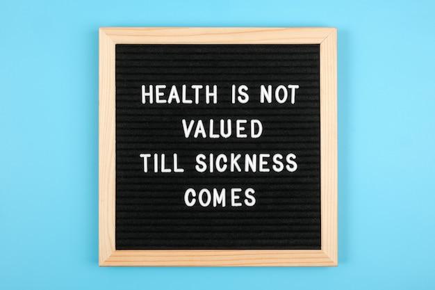 病気になるまで健康は大切にされません。青の背景に黒のレターボードに動機付けの引用。コンセプトヘルスケア