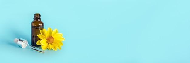 Эфирное масло в открытой коричневой капельнице и желтый цветок на синем фоне. концепт косметической косметики