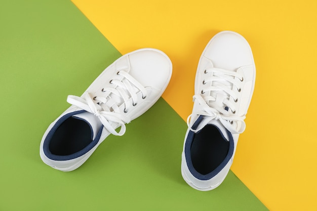緑と黄色の床に靴ひもが付いた白いスニーカー