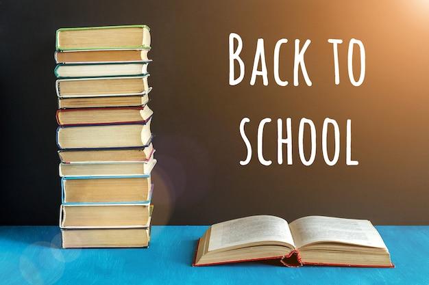 黒い黒板と開いた本、青いテーブルの上の本のスタック上の学校のテキストに戻る。