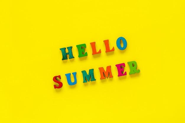 黄色の背景にカラフルな文字から碑文こんにちは夏、