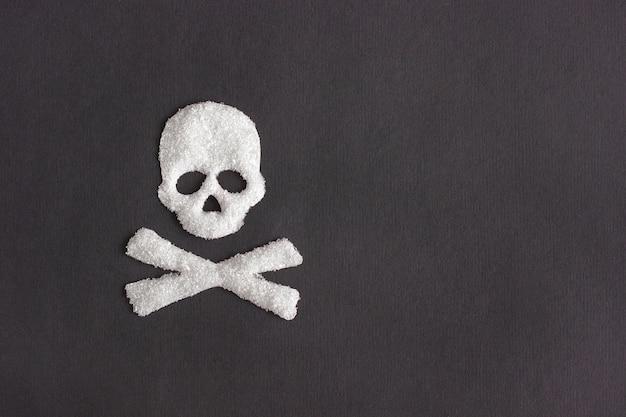 黒の背景、概念上の砂糖から頭蓋骨形状