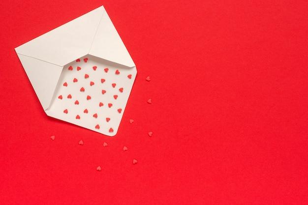 赤の背景にホワイトペーパー封筒から飛ぶ赤いお菓子の心を振りかける