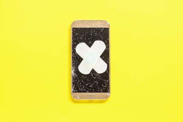 黄色の石膏で固定ひびの入った画面を持つモバイルスマートフォン