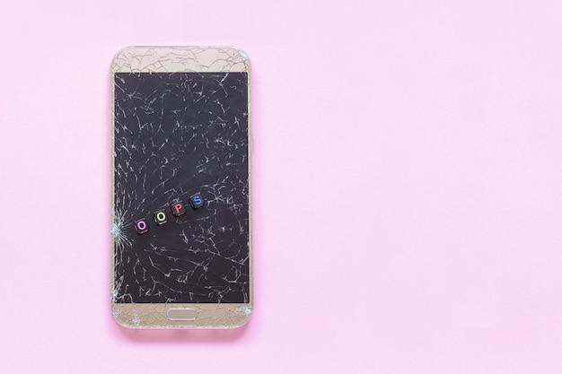 壊れたひび割れ携帯電話とピンクの背景のテキストおっと