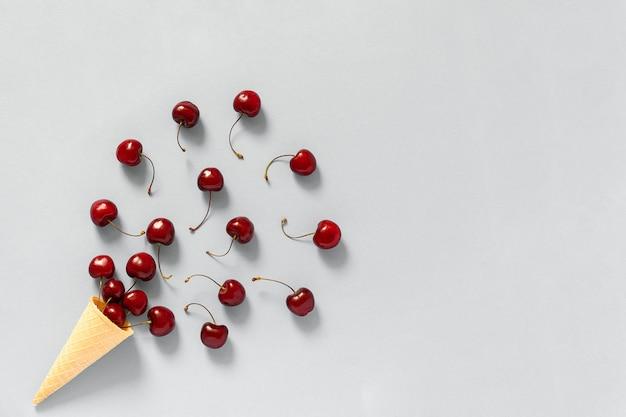 Вафельный рожок с разбросанной красной спелой черешней.
