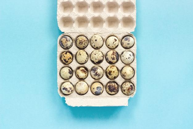 青い紙の背景に段ボール箱にウズラの卵。