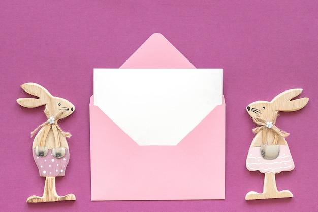 ロマンチックな構図木製恋人たちの置物ウサギとピンクの封筒