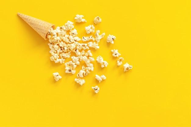 黄色の紙の背景にアイスクリームワッフルコーンに散在ポップコーン