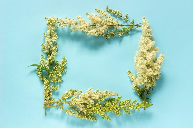 花の組成青い背景に咲く小枝白い花のフレーム自然花の長方形の花輪