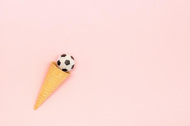 Футбол или футбольный мяч в вафельном конусе мороженого на розовой предпосылке в минимальном стиле.