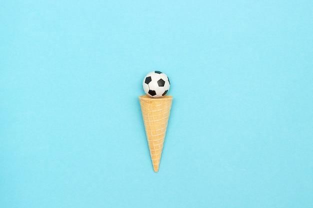 Футбол или футбольный мяч в вафельном рожке мороженого. концепция спортивных развлечений.