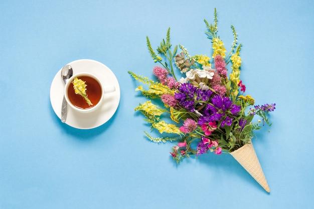 ワッフルアイスクリームコーンと紅茶のカップでフィールドのカラフルな花
