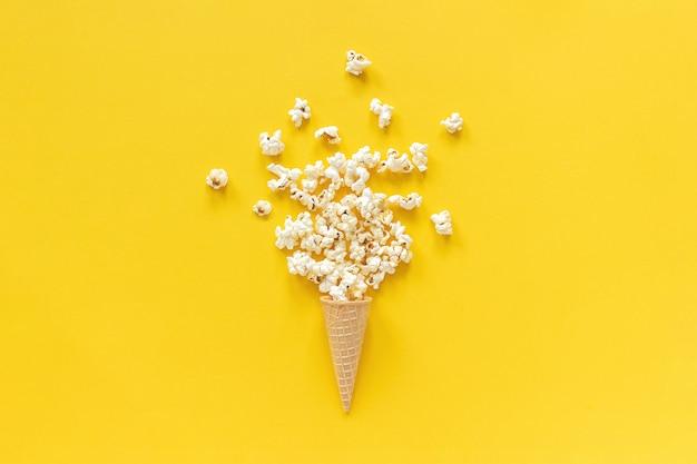 黄色の紙の背景にアイスクリームワッフルコーンに散在するポップコーン。