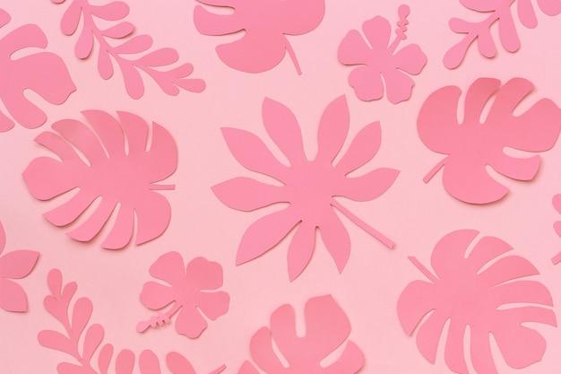 熱帯の葉のパターン。ピンクの背景の紙のトレンディなピンクの熱帯の葉。