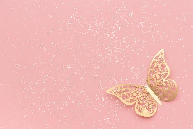 ピンクのパステル調のトレンディな背景に輝くキラキラとゴールドの網目模様の蝶。
