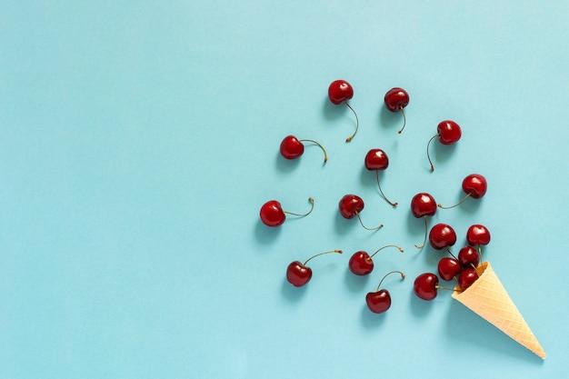 Вафельный рожок мороженого и разбросанные красные черешни