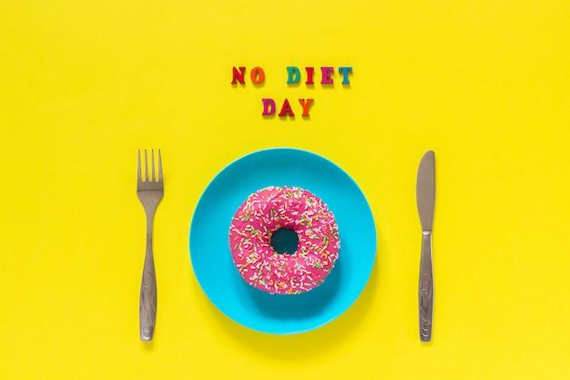 Текст без диеты день, пончик на тарелку и столовые приборы стол нож вилка.