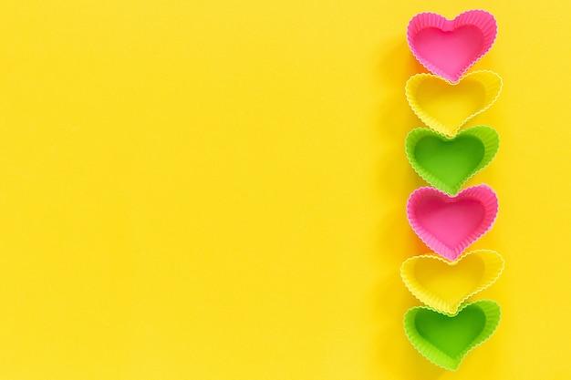 黄色の背景に行の右側に並ぶカップケーキを焼くための着色されたシリコンハート型の金型皿。