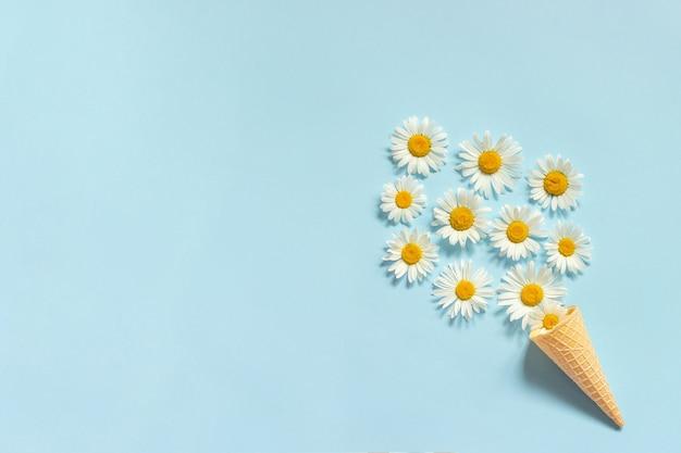 青い背景にワッフルアイスクリームコーンの花束カモミールの花